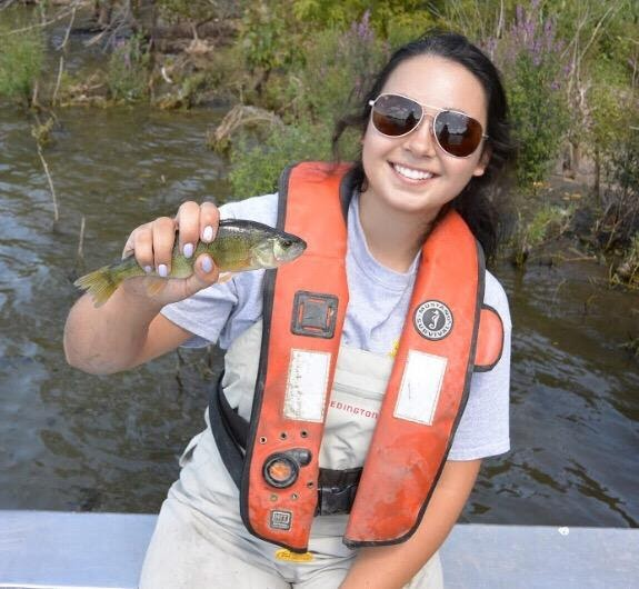Lianne Girard near a body of water holding a small fish in her hand.
